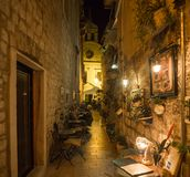 Restaurant, coffee place, winery in the center of Sibenik town, outside seating in a small narrow street with a church Stock Image
