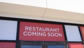 Restaurant Coming Soon. A window sign lets people know that a fine dining food eatery restaurant will be opening soon in this location royalty free stock photos