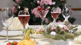 Restaurant concept. New Year and Merry Christmas feast table. champagne bubbles in glass. Sliced fruit dish, cheese. Plate and champagne in glasses are stock video footage