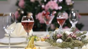 Restaurant concept. New Year and Merry Christmas feast table. champagne bubbles in glass. Sliced fruit dish, cheese. Plate and champagne in glasses are stock footage