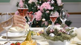 Restaurant concept. New Year and Merry Christmas feast table. female hands takes, holds and then puts a glass of. Champagne with bubbles. 4k stock video footage