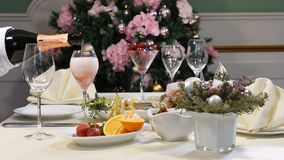 Restaurant concept. New Year and Merry Christmas feast table. Waiter in gloves pours champagne out of the bottle. Sliced. Fruit dish and cheese plate are stock video
