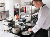 Restaurant chef lifestyle work kitchen cook. Restaurant cook lifestyle. Chef working at the stove in a kitchen Stock Photos