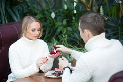 Restaurant, couple and holiday concept - excited young woman looking at boyfriend with engagement ring Royalty Free Stock Images