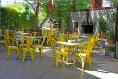 Restaurant courtyard with yellow chairs under the trees royalty free stock images