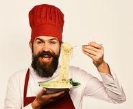 Restaurant cuisine concept. Chef eats italian or asian noodles. Cook with cheerful face in burgundy uniform holds fork and plate. Man with beard holds tasty stock photography