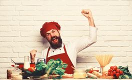 Restaurant cuisine concept. Chef prepares meal. Man with beard. Makes winning gesture on white brick wall background. Cook with cheerful face in uniform sits by stock image