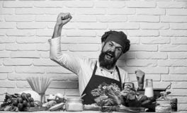 Restaurant cuisine concept. Chef prepares meal. Man with beard. Makes winning gesture on white brick wall background. Cook with cheerful face in uniform sits by stock images