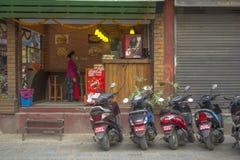 Restaurant d'aliments de préparation rapide de rue avec des motos garées et un intérieur de femme photographie stock libre de droits