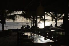 Restaurant de bord de mer, terrasse de barre, silhouettes d'amis au coucher du soleil Photographie stock libre de droits