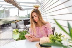 Restaurant de véranda de café d'été de fille Repose le smartphone de main de table, Internet de causerie, correspondance d'applic image libre de droits