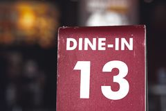 Restaurant dine in table top sign holders. Queueing serving unlucky number 13. With dark moody bokeh background royalty free stock photos