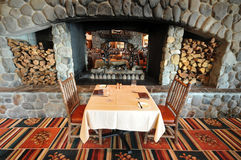 Restaurant dining table with fireplace and logs Royalty Free Stock Photo