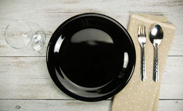 Restaurant dinner place setting. Elegant table setting with fork, spoon, glass and dot brown napkin Stock Images