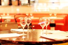 Empty restaurant background with wineglasses and napkins in front of abstract blurred restaurant lights, Paris, France. A restaurant dinner table place setting stock images
