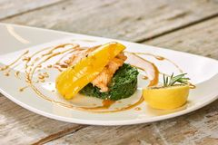 Restaurant dish with salmon, bell pepper, lemon and greens. Fancy dish with salmon, yellow sauce, bell pepper, lemon and greens stock photos