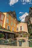 Restaurant with flowers and cliffs in Moustiers-Sainte-Marie. stock image