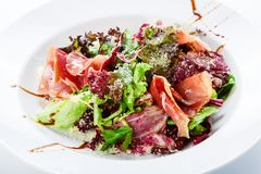 Restaurant food closeup - salad with prosciutto and vegetables Stock Photography