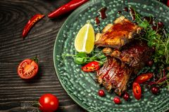 Restaurant food concept. pork ribs grilled with BBQ sauce. Tasty snack served with green seedlings on the plate. restaurant royalty free stock image