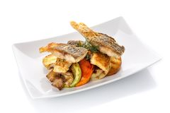 Fried fish with vegetables on a plate.  on white Royalty Free Stock Image