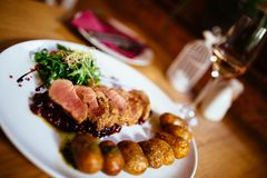 Restaurant food with fresh ingredients. Pork tenderloin with grenaille potatoes and fresh salad in luxury restaurant environment, cutlery and glass of wine stock image
