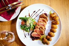 Restaurant food with fresh ingredients. Pork tenderloin with grenaille potatoes and fresh salad in luxury restaurant environment, cutlery and glass of wine royalty free stock images
