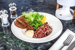 Close up view on served Steak beef tartare served with lemon, bread, sauce and salad on marble table. royalty free stock images