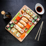 Restaurant food. Sushi rolls, soy sauce and traditional chopsticks on a black background. Top view. Flat lay. Royalty Free Stock Images