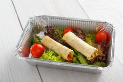 Restaurant food take away closeup in foil box, crepe rolls with vegetables Royalty Free Stock Photos