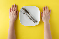 Restaurant and Food theme: the human hand show gesture on an empty white plate on a yellow background in studio isolated top view stock image