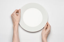Restaurant and Food theme: the human hand show gesture on an empty white plate on a white background in studio isolated top view Stock Photos