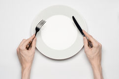 Restaurant and Food theme: the human hand show gesture on an empty white plate on a white background in studio isolated top view Stock Image