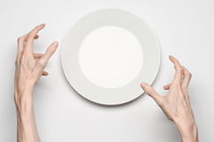 Restaurant and Food theme: the human hand show gesture on an empty white plate on a white background in studio isolated top view Royalty Free Stock Photography