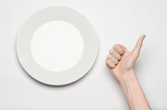 Restaurant and Food theme: the human hand show gesture on an empty white plate on a white background in studio isolated top view Royalty Free Stock Photos