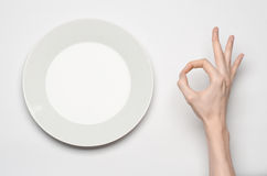 Restaurant and Food theme: the human hand show gesture on an empty white plate on a white background in studio isolated top view Royalty Free Stock Images