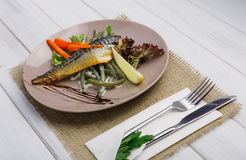 Restaurant food on wooden table. Smoked mackerel with vegetables closeup Royalty Free Stock Photo