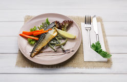 Restaurant food on wooden table. Smoked mackerel with vegetables Royalty Free Stock Photo