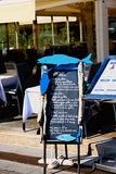 Restaurant in France. Typical  scene in France with menu board and tables and chairs arranged on the street Stock Images