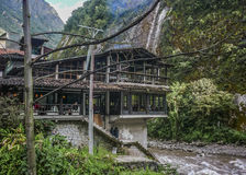Restaurant in Front of Urubamba River in Aguas Calientes. Picturesque restaurant in front of Urubamba river with big mountains at background in Aguas Calientes royalty free stock images
