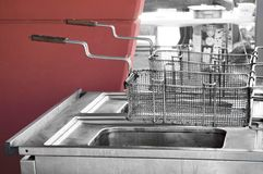 Restaurant fryer. Double used restaurant fryer in open space by a red wall Stock Images
