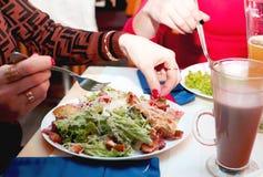 Girls eat Caesar salad in the restaurant stock photography