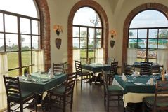 Restaurant with Grand Window View of lush green and blue seas. Restaurant with green tables and wooden chairs with grand arched  window view of outdoor lush Royalty Free Stock Photography