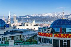 Restaurant with green plant on roof of modern high-rise building overlooking snow-covered mountains. Batumi, Georgia, 11-25-2017: Rational use of urban space Royalty Free Stock Photo