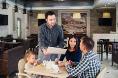 Restaurant and holiday concept - waiter giving menu to happy family at cafe Royalty Free Stock Photo