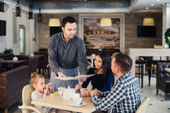 Restaurant and holiday concept - waiter giving menu to happy family at cafe Stock Photo