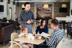 Restaurant and holiday concept - waiter giving menu to happy family at cafe Stock Image