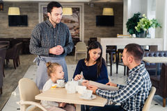 Restaurant and holiday concept - waiter giving menu to happy family at cafe Stock Photography