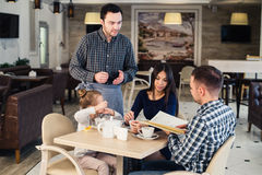 Restaurant and holiday concept - waiter giving menu to happy family at cafe. Restaurant and holiday concept - waiter giving menu to happy family at restaurant Stock Photography