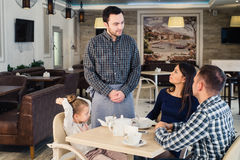 Restaurant and holiday concept - waiter giving menu to happy family at cafe Royalty Free Stock Images