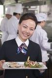 Restaurant Hostess Presenting Gourmet Dish Stock Image